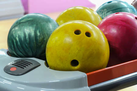 Several shabby bowling balls of different colors and weights on stand. Bowling equipment. Active leisure. Sports activities for whole family. Space for text. Selective soft focus, blurred background