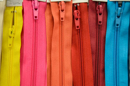 Close-up of multicolored zippers placed vertically in a sewing shop. Accessories for making clothes, textiles. Concept of haberdashery. Stockfoto