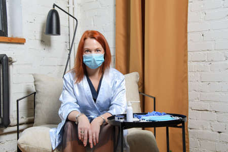 Young woman with red hair in medical mask shocked upon learning of positive test . The concept of confusion, uncertainty, stress, shock, fear for your life and health.