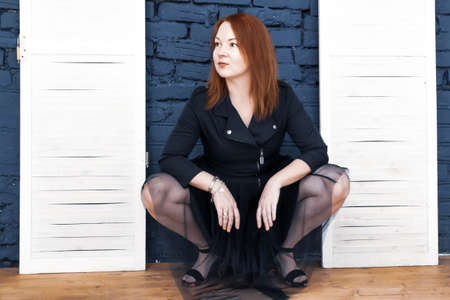 Red-haired young woman in blue dress sits on his haunches against a background of blue brick wall and white wooden doors. Looking to the side. Vulgar pose, flirting, attracting attention