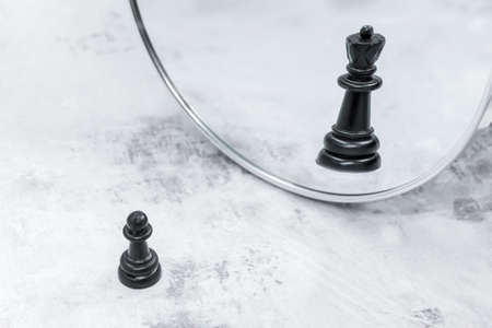 Black chess pawn in front of mirror sees reflection of chess queen. The concept of career growth, transformation. Proverb illustration: soldier who doesn't want to be general is bad soldier