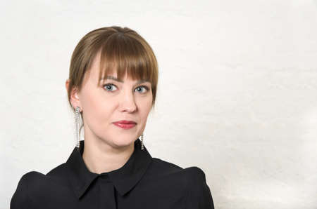 Young woman with hair pulled back and bangs in black dress with round collar against white wall. Minimalistic full face portrait. Woman portrait for business presentation, top manager, business woman Banque d'images