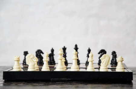 Close-up of chess pieces placed on chessboard at beginning of the game. Concept: tactics, preparation for game, chess strategy. International Chess Day. Copyspace