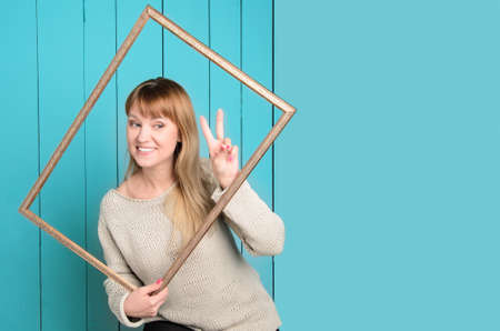 Beautiful pretty blonde young woman in knitted pullover with loose hair holds vintage wooden picture frame showing finger V sign and smiles. On background light blue wood background. Copyspace