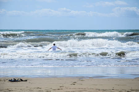 Man in white T-shirt with his arms apart enters the sea in strong storm. Beach shoes were left in sand. Swimming during a storm, security breach on the beach.