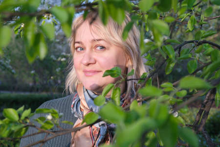 Portrait of a middle-aged woman with blond hair through tree branches with leaves. Flirty look and a light smile. A walk in spring park, romantic date, woman in love.