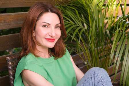 Portrait of a young attractive woman with red hair and bright red lips in jeans and a green short sleeve blouse. Woman is sitting on a wooden bench among green plants and smiling.