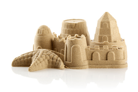 Sandcastle at the beach isolated over white  Standard-Bild
