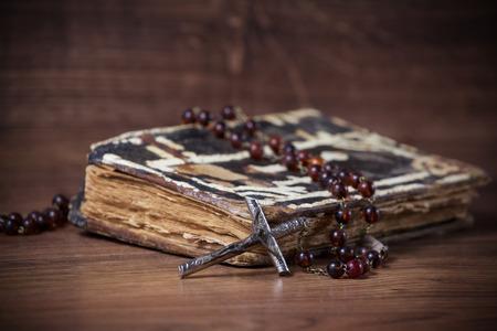 hymn: Christian cross necklace next to prayer-book Stock Photo
