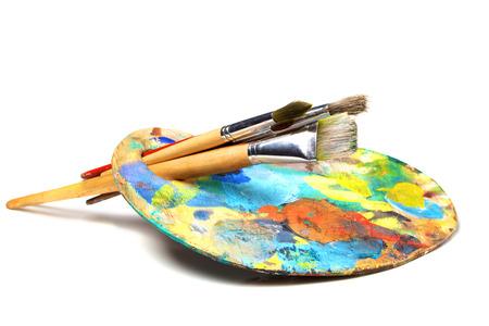 palet: Paleta de arte con pintura y un pincel sobre fondo blanco