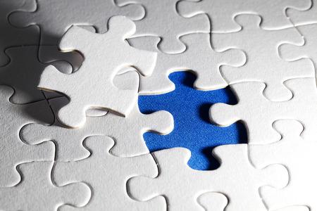Plain white jigsaw puzzle, on Blue background, autism awerness symbol photo