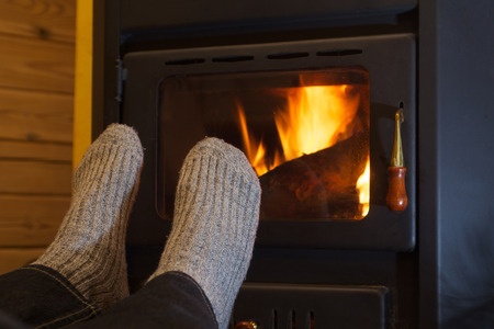 stockings feet: feet in stockings by the fireplace Stock Photo