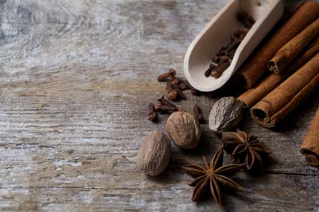 nutmeg: Spices on wooden background. Cinnamon, nutmeg, cloves, anise