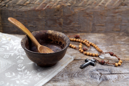 Fasting, Lent. Cup and cross. on wooden background