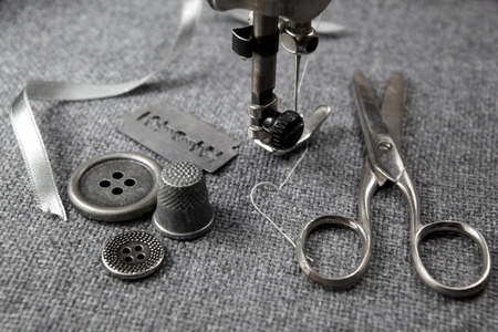 textile machine: sewing machine with tools on fabric background