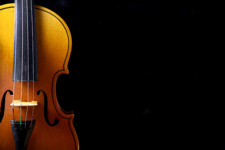 vintage music background: Close up of a violin isolated on a black background