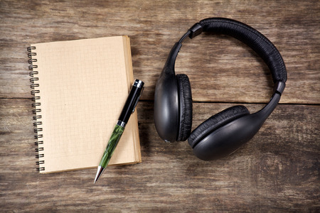 decibel: Vintage Headphones and paper note on wooden background