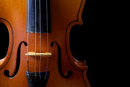 Close up of a violin isolated on a black background photo