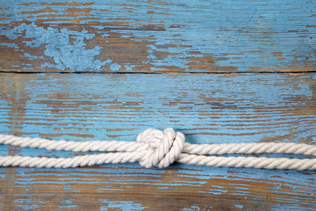 rope background: Marine knot on blue wooden background