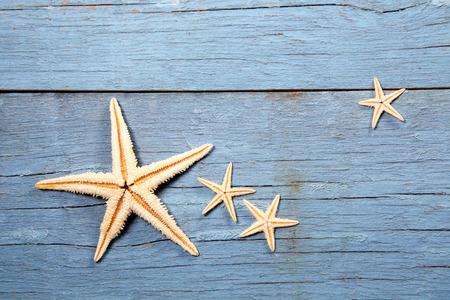 verano: estrellas de mar sobre fondo de madera azul Foto de archivo