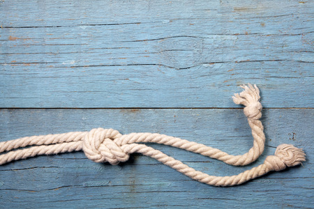 natural rope: Marine knot on blue wooden background