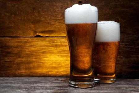 vasos de cerveza: dos vasos de cerveza sobre fondo de madera de la vendimia