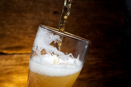 glass of water: Beer into glass on a old wooden background