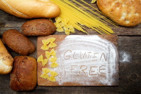 gluten free  word with bread on wood background Standard-Bild