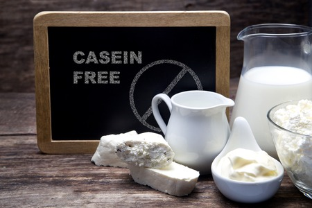 sideboard: Milk and Camembert cheese on sideboard with blackboard with inscription casein free
