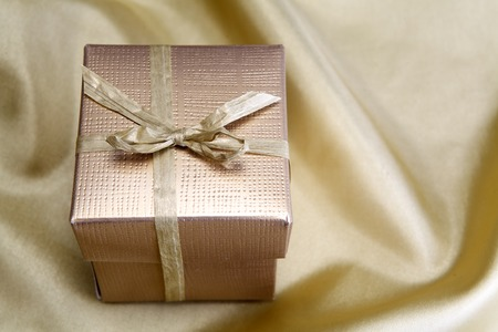 pretty s shiny: Golden box with ribbon on golden silk background