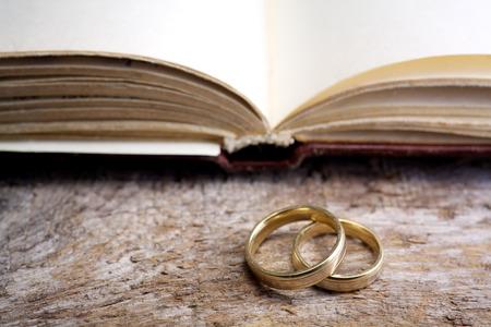 biblia: Dos anillos de boda con una biblia en mesa de madera