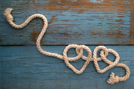 knots: leash  rope into heart shape on wooden table