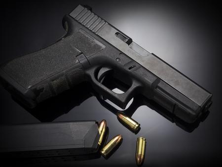 shot gun: Pistol gun with ammo on dark background Stock Photo