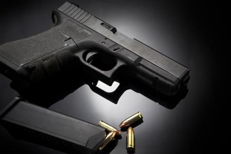 vintage gun: Pistol gun with ammo on dark background Stock Photo
