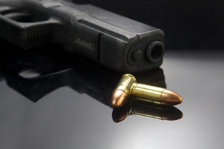 暗い背景上の弾薬が付いているピストル銃