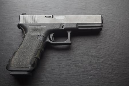 marksmanship: hand pistol gun on dark black background