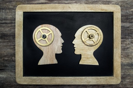 Two human head silhouettes with gears on wooden background Stock Photo