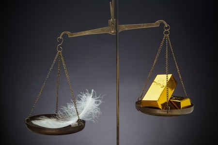 overbalance: The feather outweighs a stacks of golden bars on the scale Stock Photo