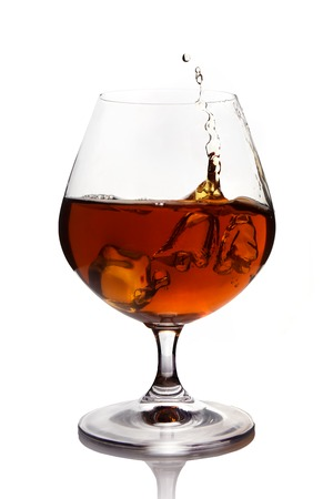 Splash of cognac in glass isolated on white