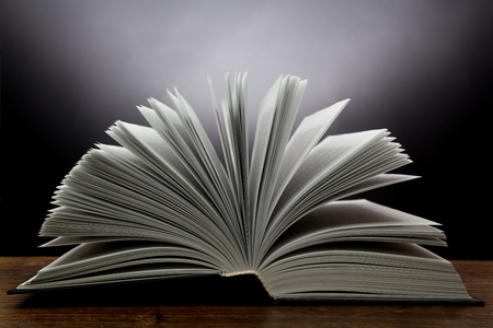 open space: Old open book with light on a dark abstract background