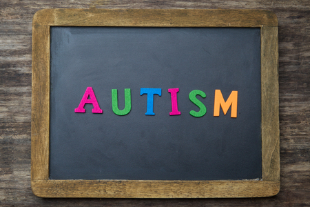 developmental disorder: the word autism written on a rustic wooden desk or table