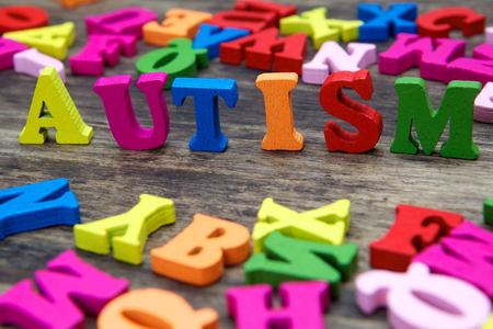 and spelling: Colourful letters spelling out Autism on a wooden background Stock Photo