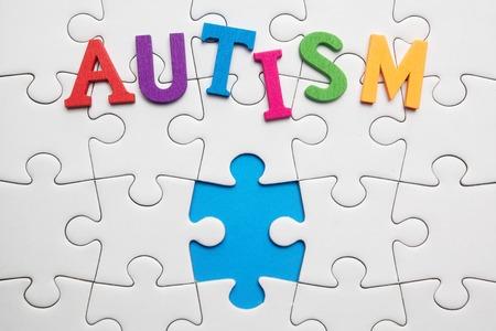 흰색 퍼즐 배경에 자폐증 비문입니다. 자폐증의 상징.
