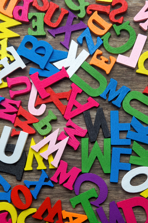 symbol  punctuation: Surface covered with multiple colored wooden letters as a background composition