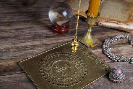 foretelling: Characterization and foretelling with pendulum on wooden table Stock Photo