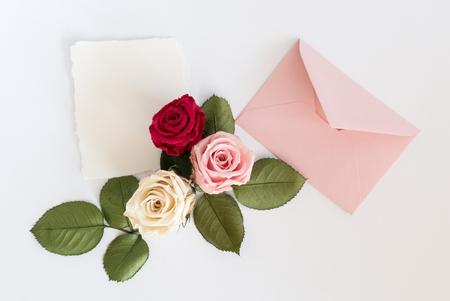粉红色信封,白色卡片和玫瑰。平躺,俯视图。