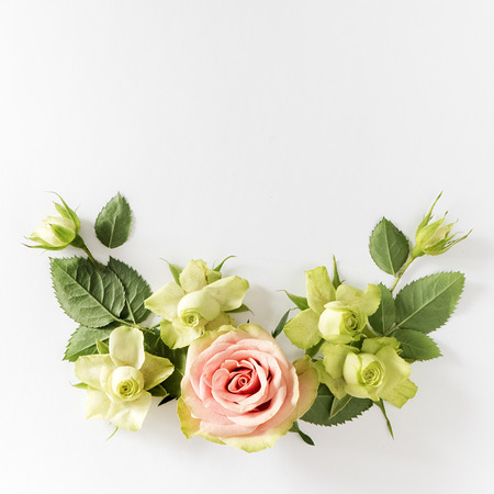 Frame  with  roses, green flowers and leaves on white background. Flat lay, top view