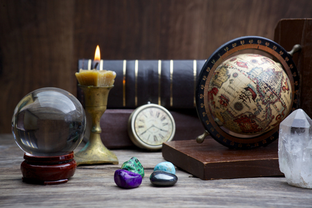 clairvoyance: Ancient astrology. Old astrology globe and books with candle Stock Photo