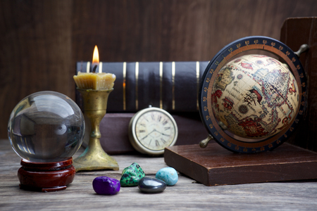 foretelling: Ancient astrology. Old astrology globe and books with candle Stock Photo