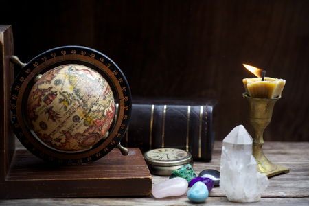 clairvoyant: Ancient astrology. Old astrology globe and books with candle Stock Photo